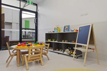 My Cubby House Southport Child Care Centre Activity Facility Brown Chair with Glass Window and Toys on Shelves