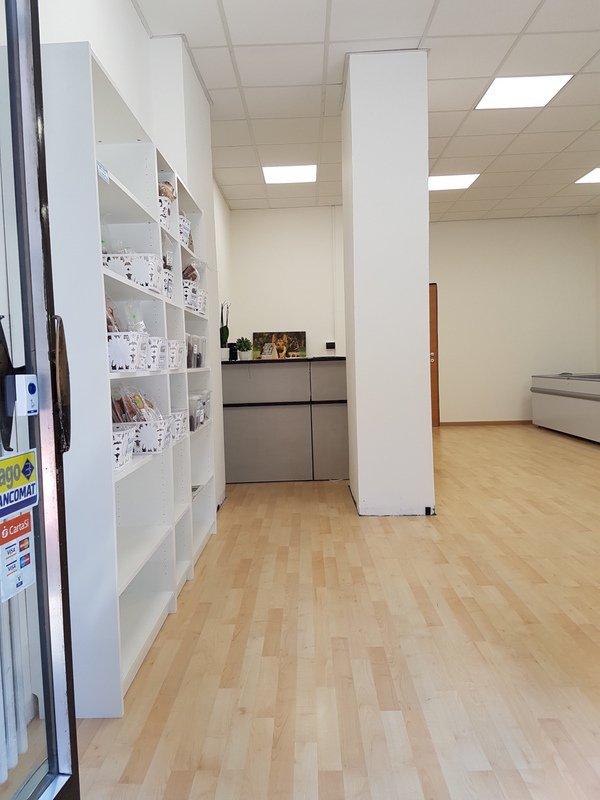 negozio con un pavimento in parquet e degli scaffali bianchi
