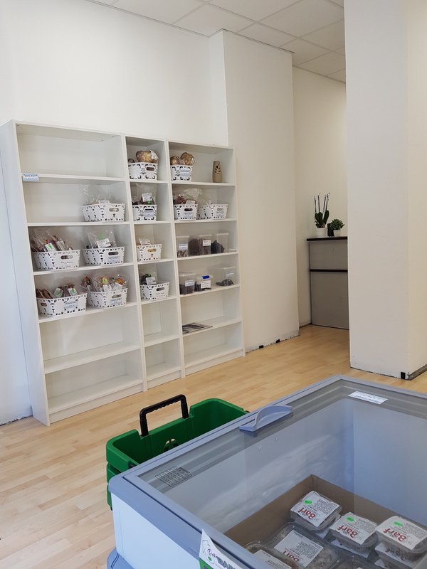 uno scaffale bianco con dei cestini e un frigorifero con del cibo per animali