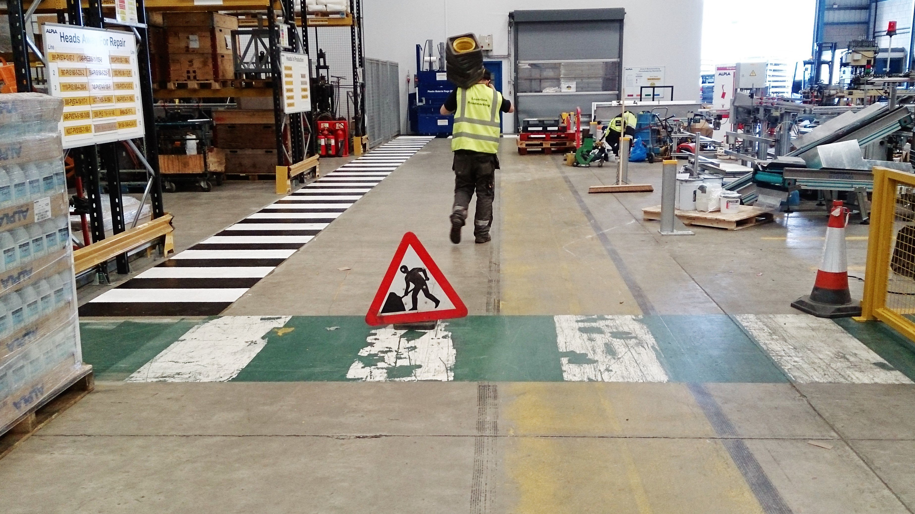 a worker painting lines on a warehouse floor