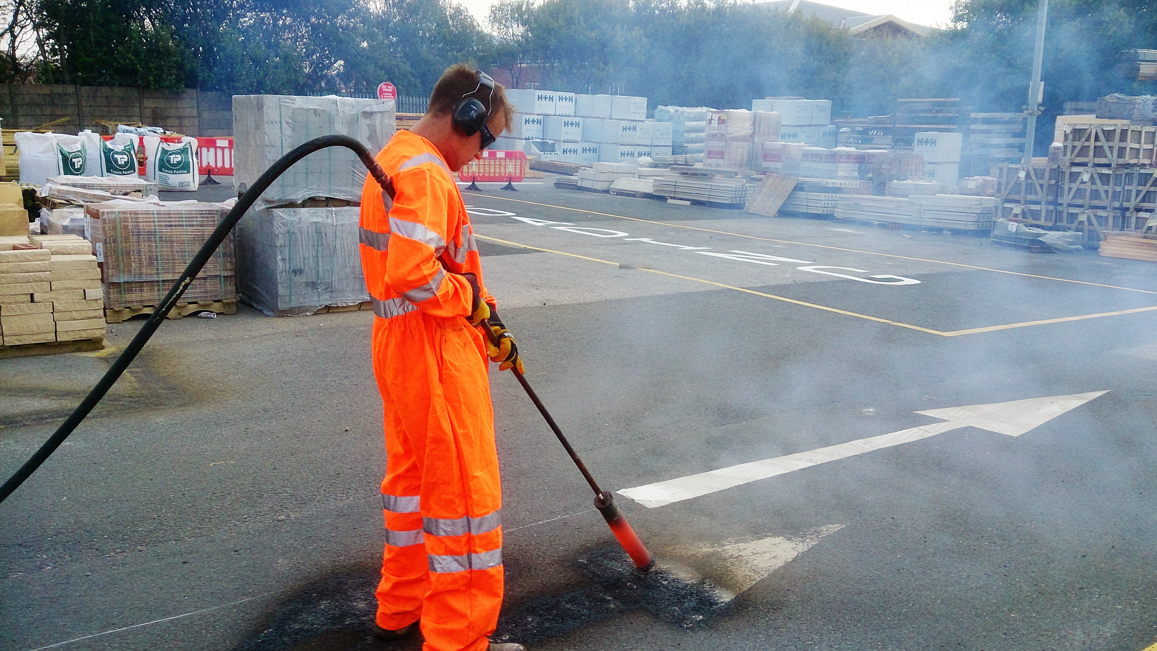 man removing thermoplastic road markings