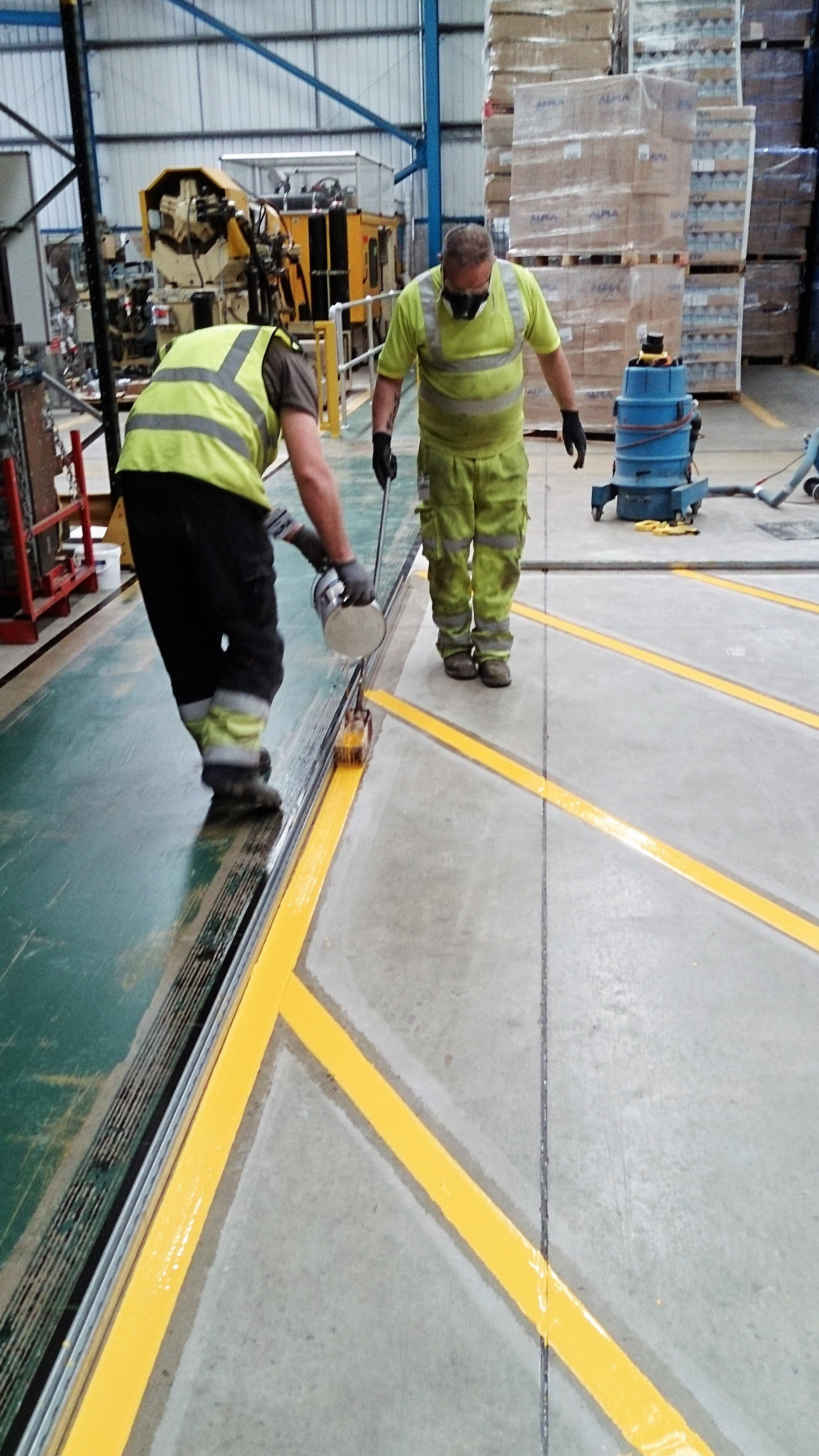 yellow line marking being applied at a warehouse indoors
