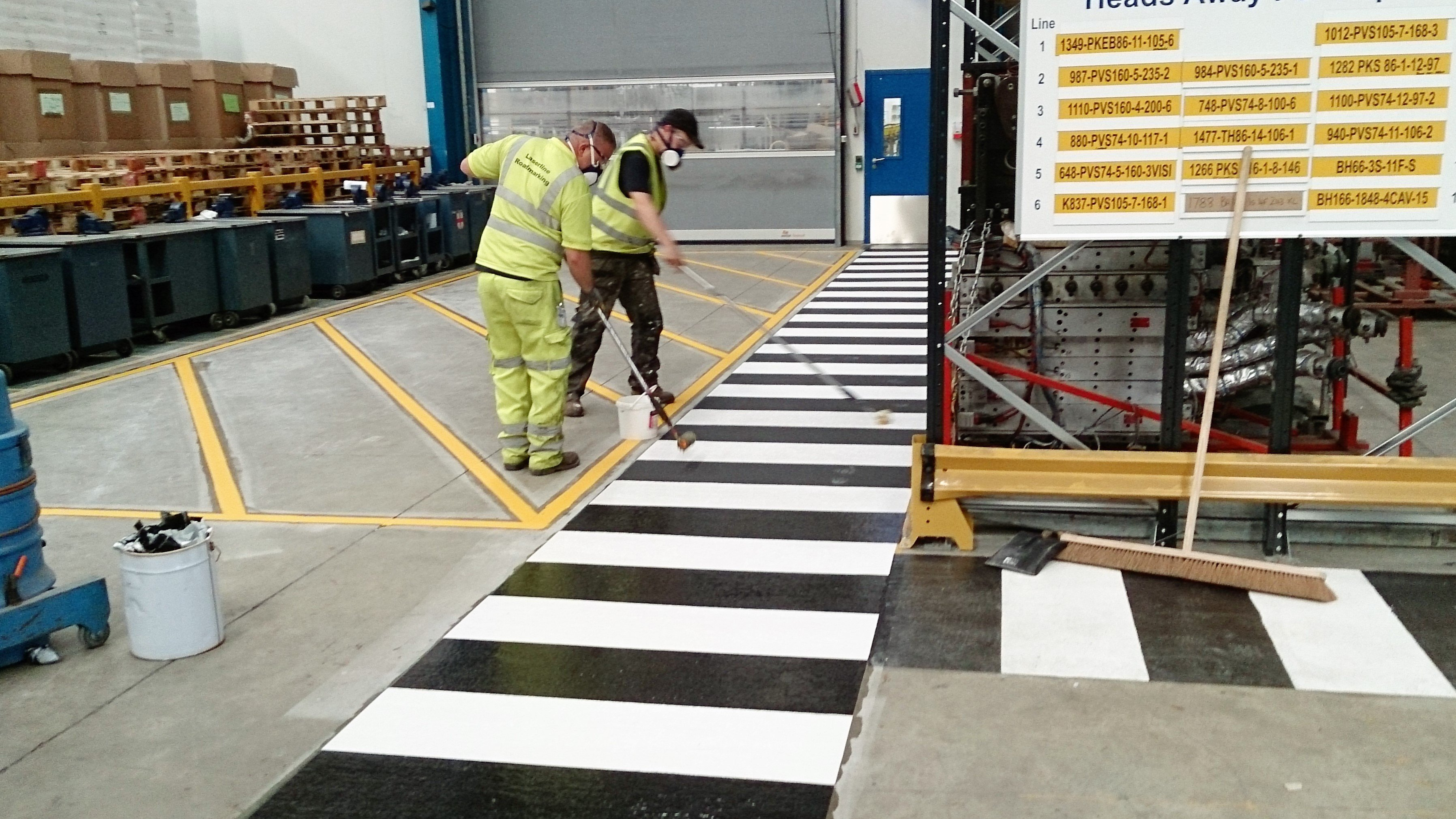 workers painting a black and white crossing