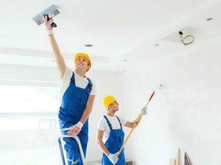 Imbianchini che pitturano una casa