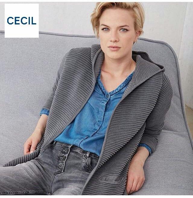 una modella della Cecil indossa una sciarpa a stelle grigia e bianca, giacca di lana bianca e jeans strappati attillati