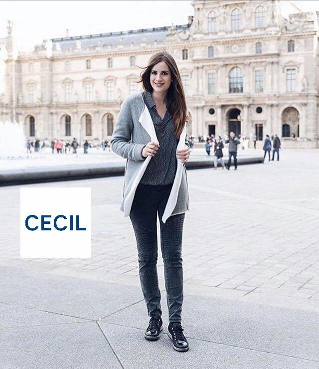 la modella indossa una mantella grigia e nera, una maglia grigia e dei blu jeans