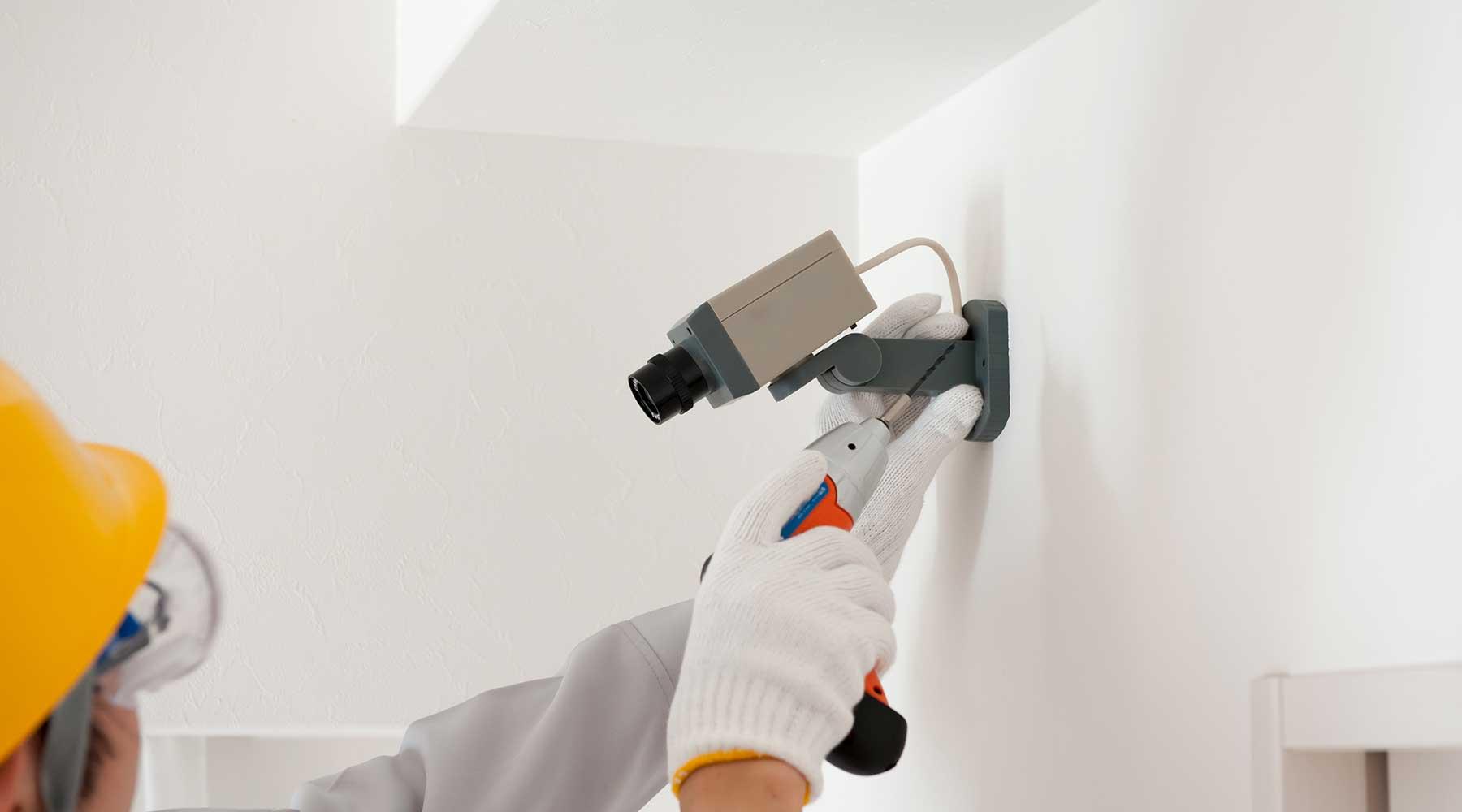 un uomo che sta installando a muro con un trapano una telecamera di sicurezza