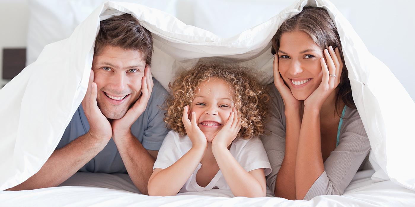 family smiling inside a blanket