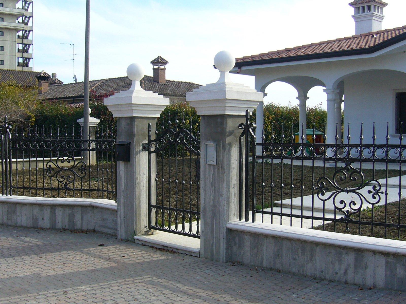 Ingresso di una casa con inferriata decorata e capitelli