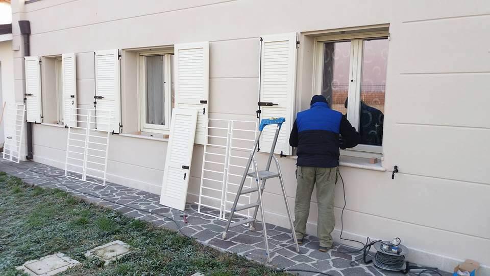 operaio mentre installa i battenti alle finestre
