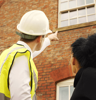 A workman pointing at a window