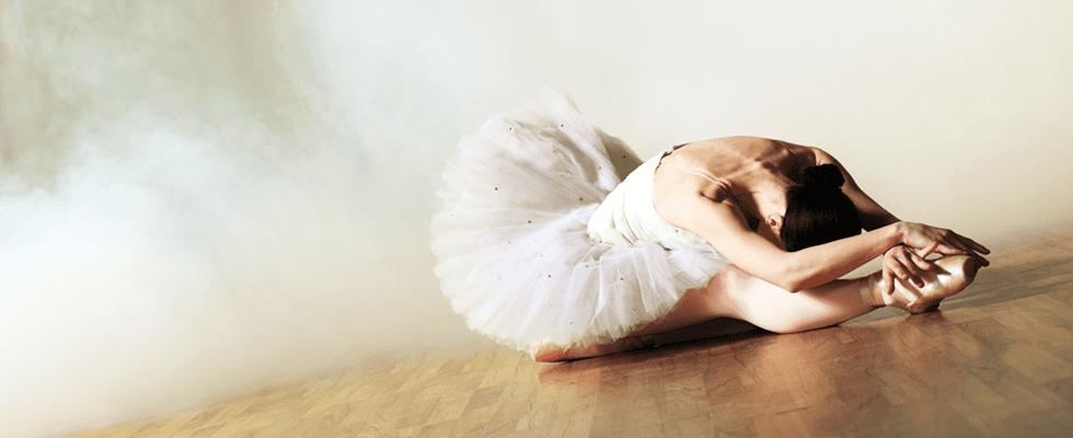 Ballerina nel suolo piegata sulla sua gamba