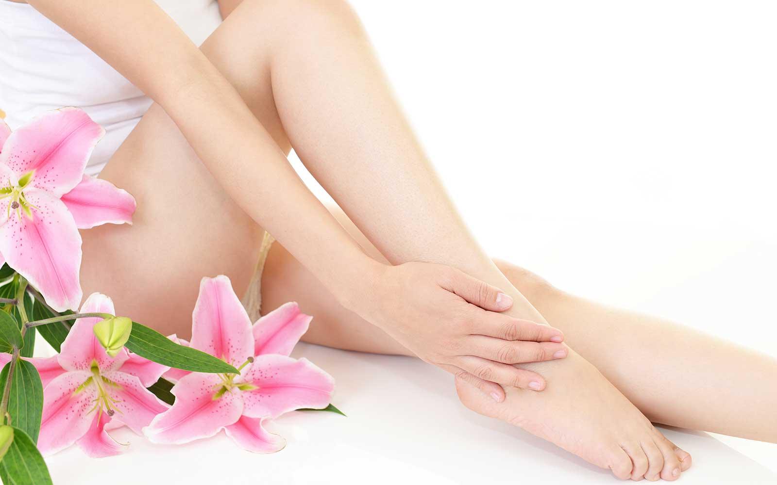 le gambe di una donna e accanto dei fiori rosa