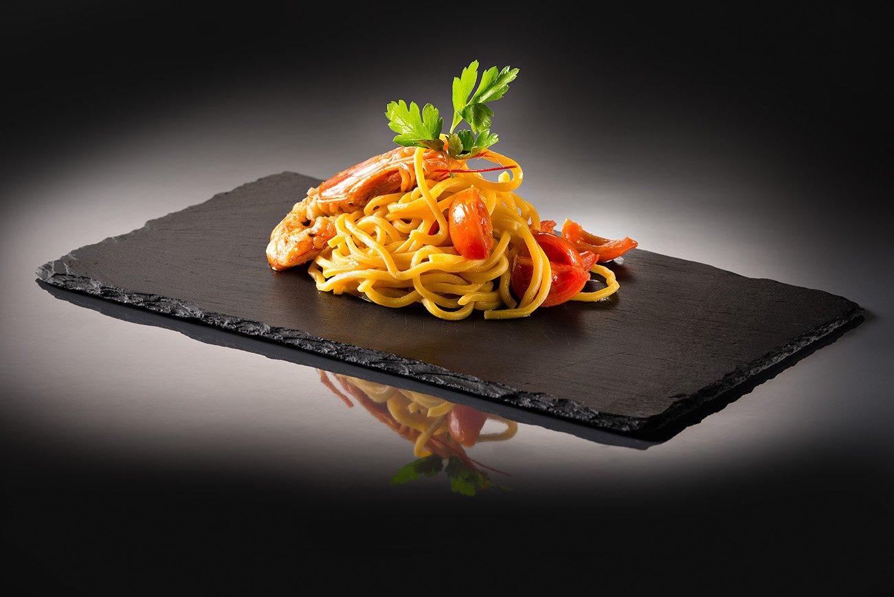 spaghetti agli scampi su un piatto nero