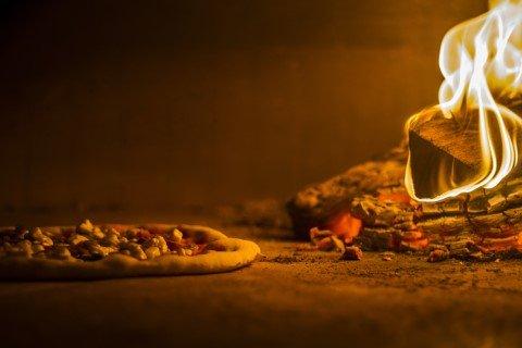 Pizza in cottura nel forno a legna