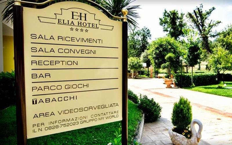 vista laterale di un cartello di ELIA HOTEL con giardino