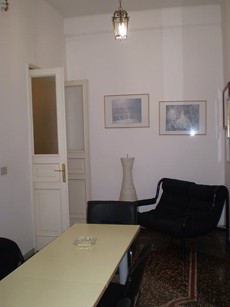un ufficio con una scrivania lucida color panna delle sedie nere, una poltrona nera, una lampada da terra e dei quadri appesi al muro