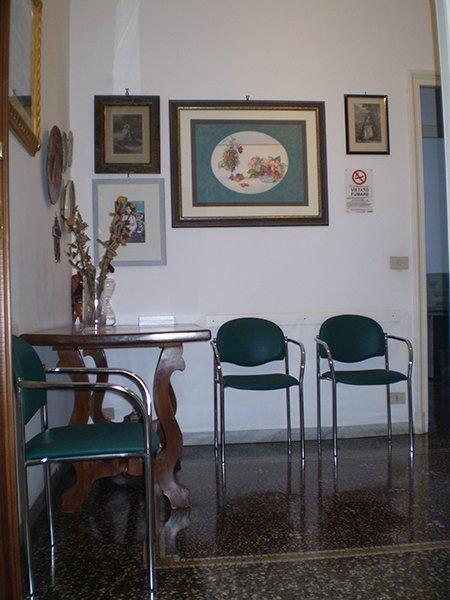 saletta con sedie in pelle verde un tavolino di legno con sopra un vaso con dei fiori e dei quadri appesi