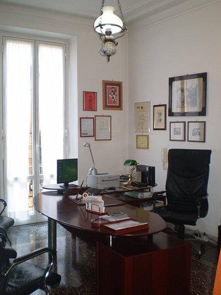 ufficio con scrivania bordeaux con sopra un monitor, una stampante e una lampada, una sedia in pelle nera e dei quadri appesi