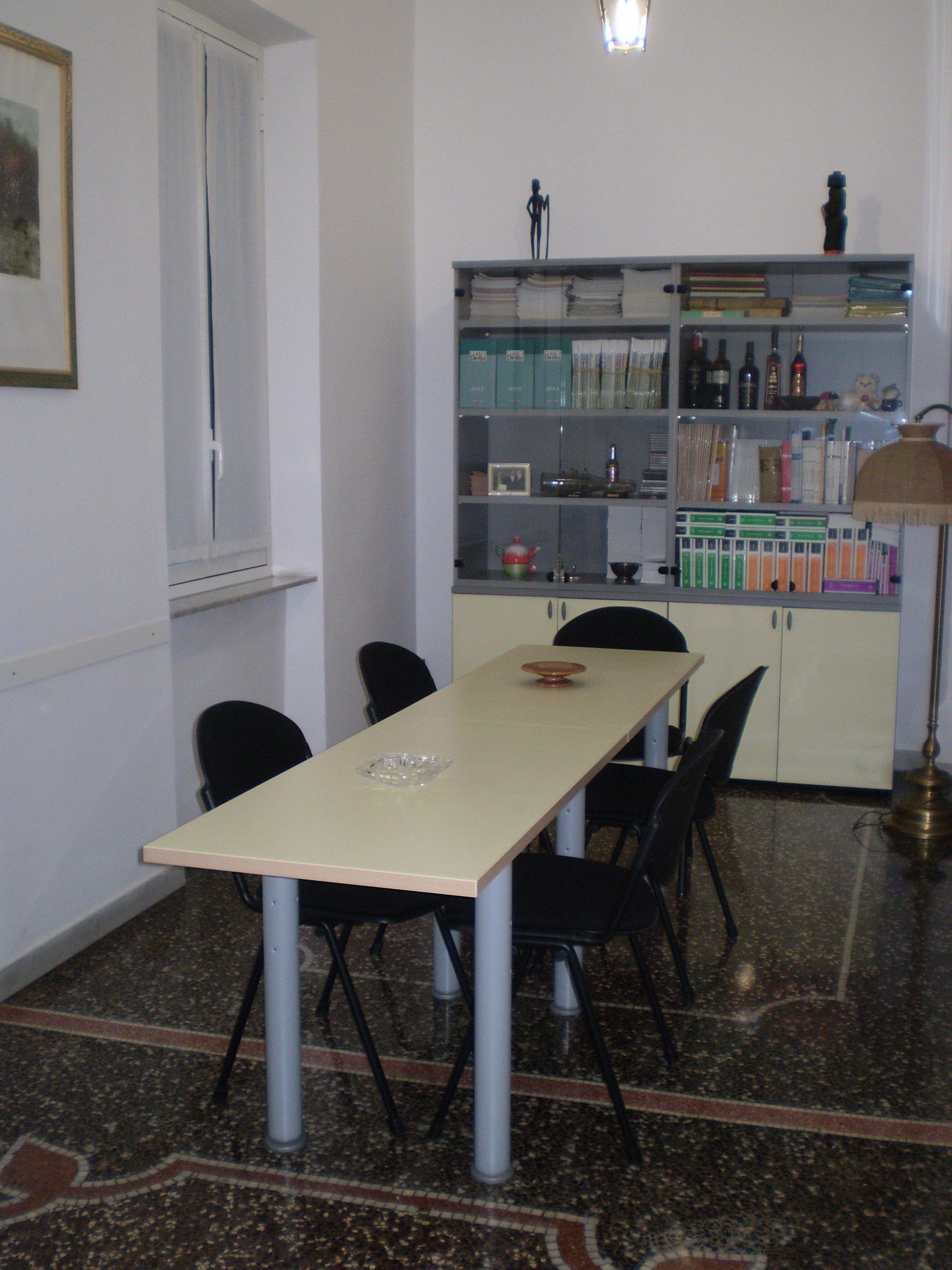 sala riunioni con tavolo bianco, sedie nere e libreria