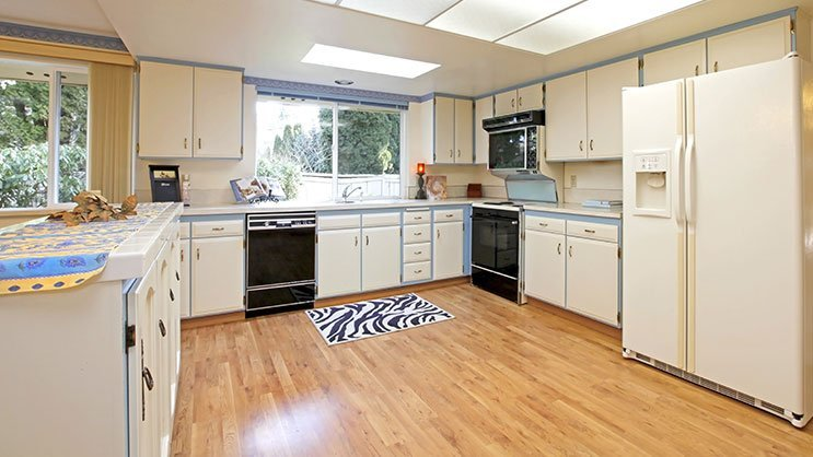 White and blue kitchen with nice hardwood floor