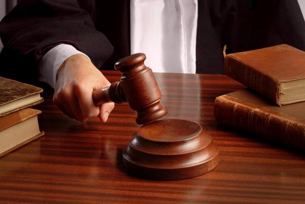 giudice tiene in mano il martelletto