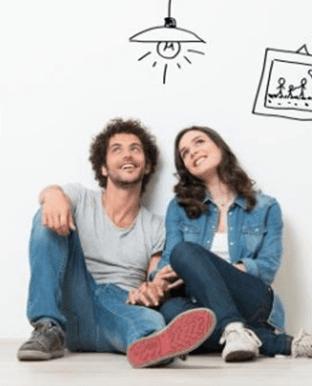 coppia sorridente seduta sul pavimento di una stanza