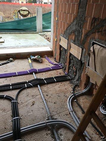 Vista dei cavi di color viola, nero e tubi grigi in un pavimento prima di essere ricoperti