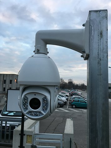 Una telecamera su un palo e più avanti delle macchine parcheggiate