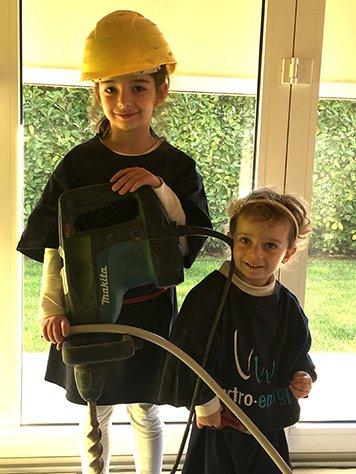 Due bambini  con trapano e pinza in mano vestiti con delle magliette nere, con scritto C.G Electro Energy