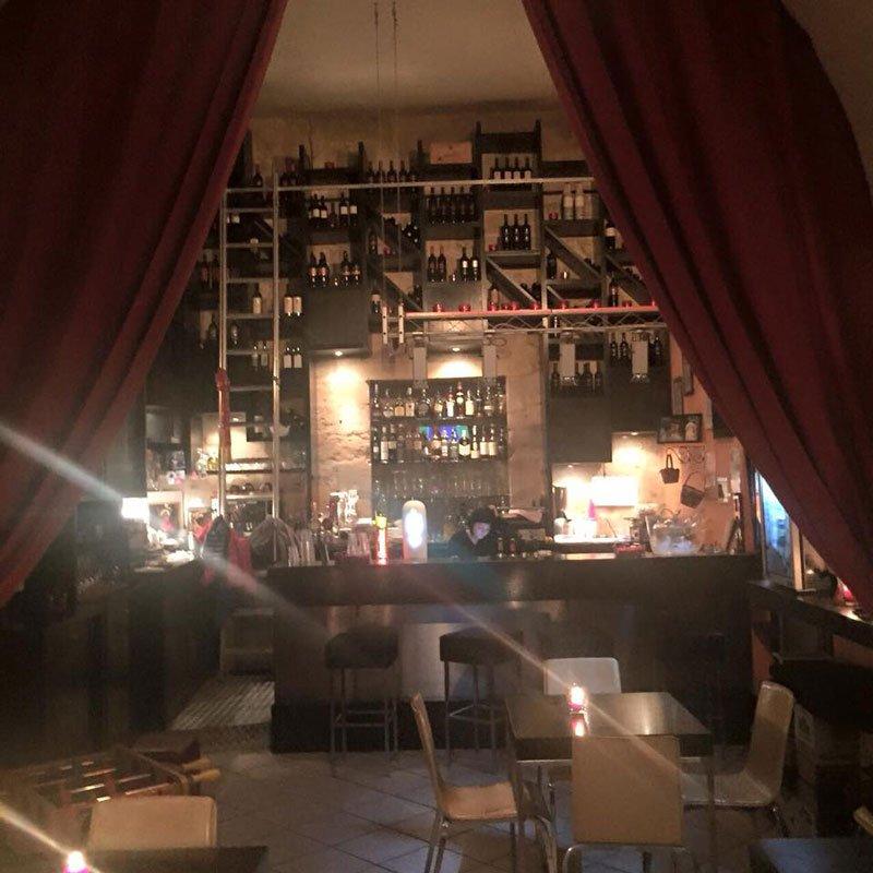 i tavoli, il bancone del bar e dietro delle bottiglie esposte