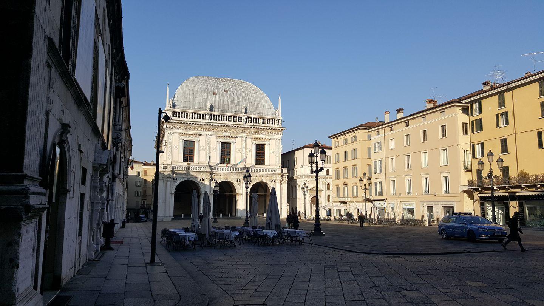 una piazza con una costruzione antica e dei tavoli con degli ombrelloni