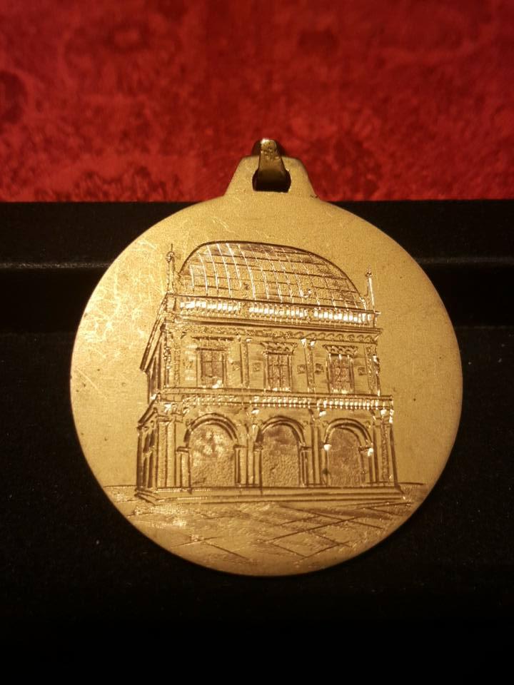 una medaglia con il disegno di un monumento