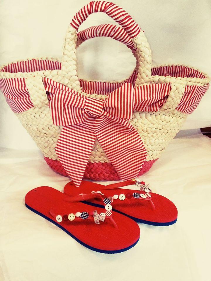 una borsa da spiaggia con un fiocco e due ciabatte rosse