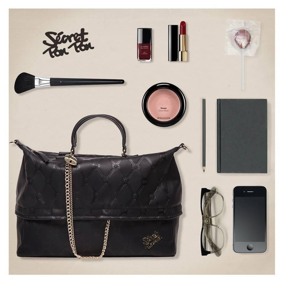una borsa nera,un paio di occhiali, un telefono e dei trucchi