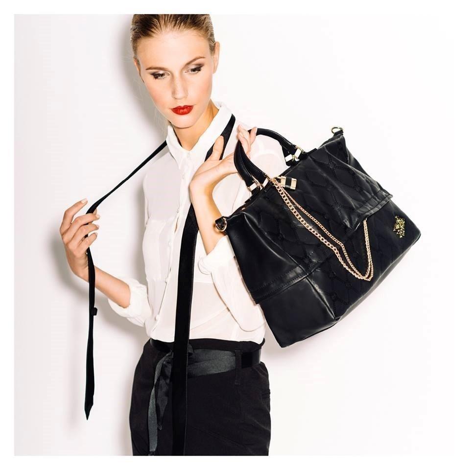 una donna bionda con in mano una borsa