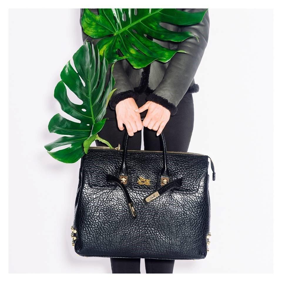 due mani che tengono una borsa di pelle nera e delle