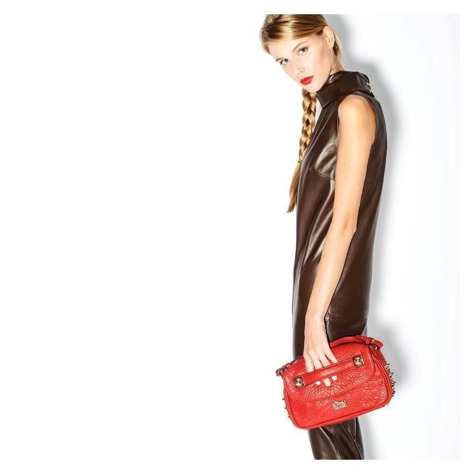 una ragazza che tiene in mano una borsetta rossa