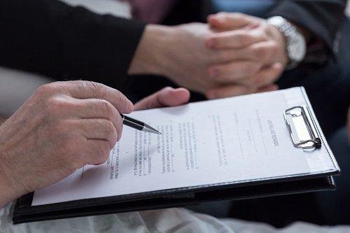 una mano con una penna in mano che scrive su un foglio