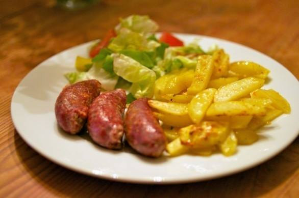 un piatto di salsiccia, patatine e dell'insalata