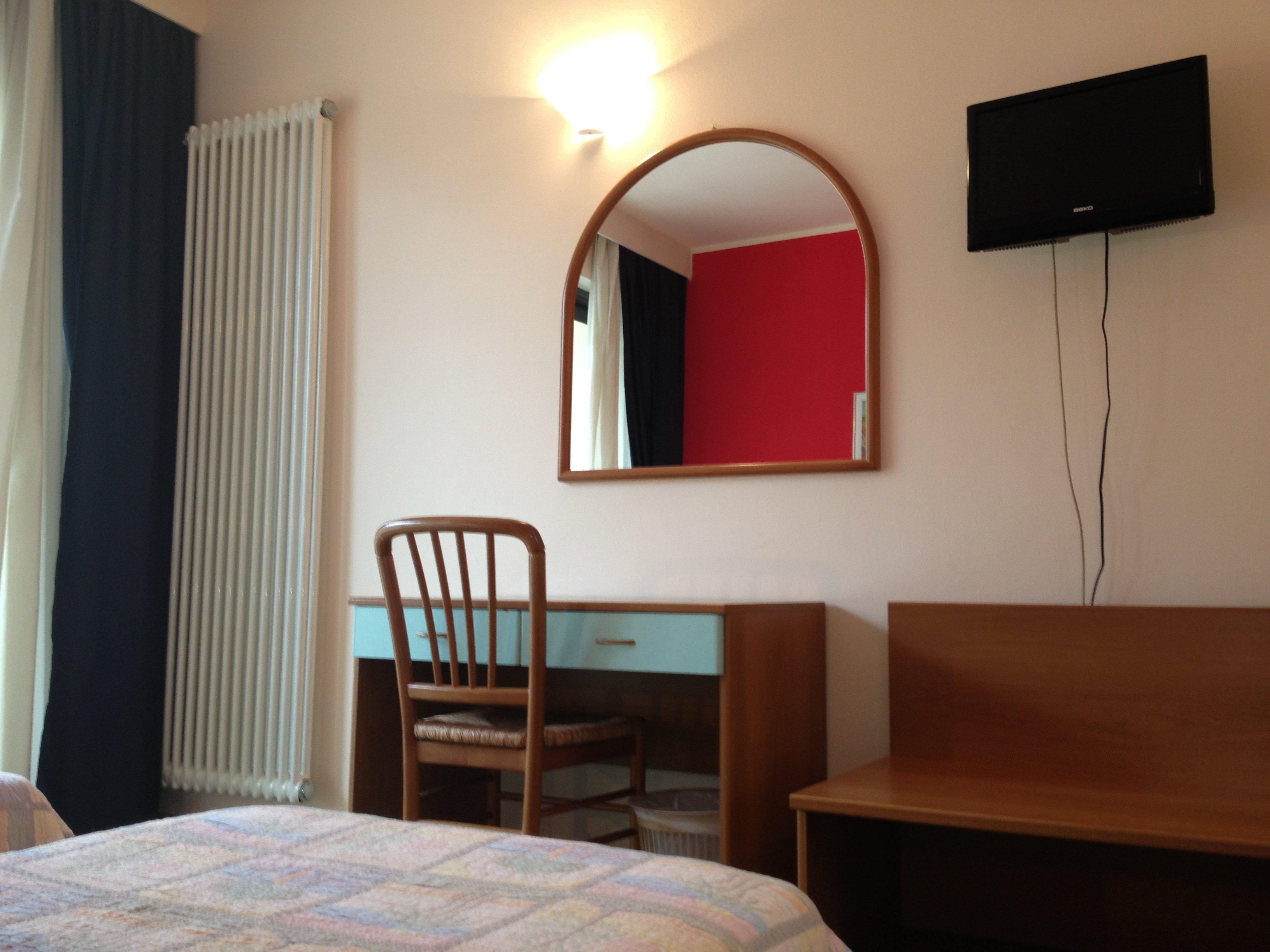 Visione di camera con scrivania, una sedia e uno specchio