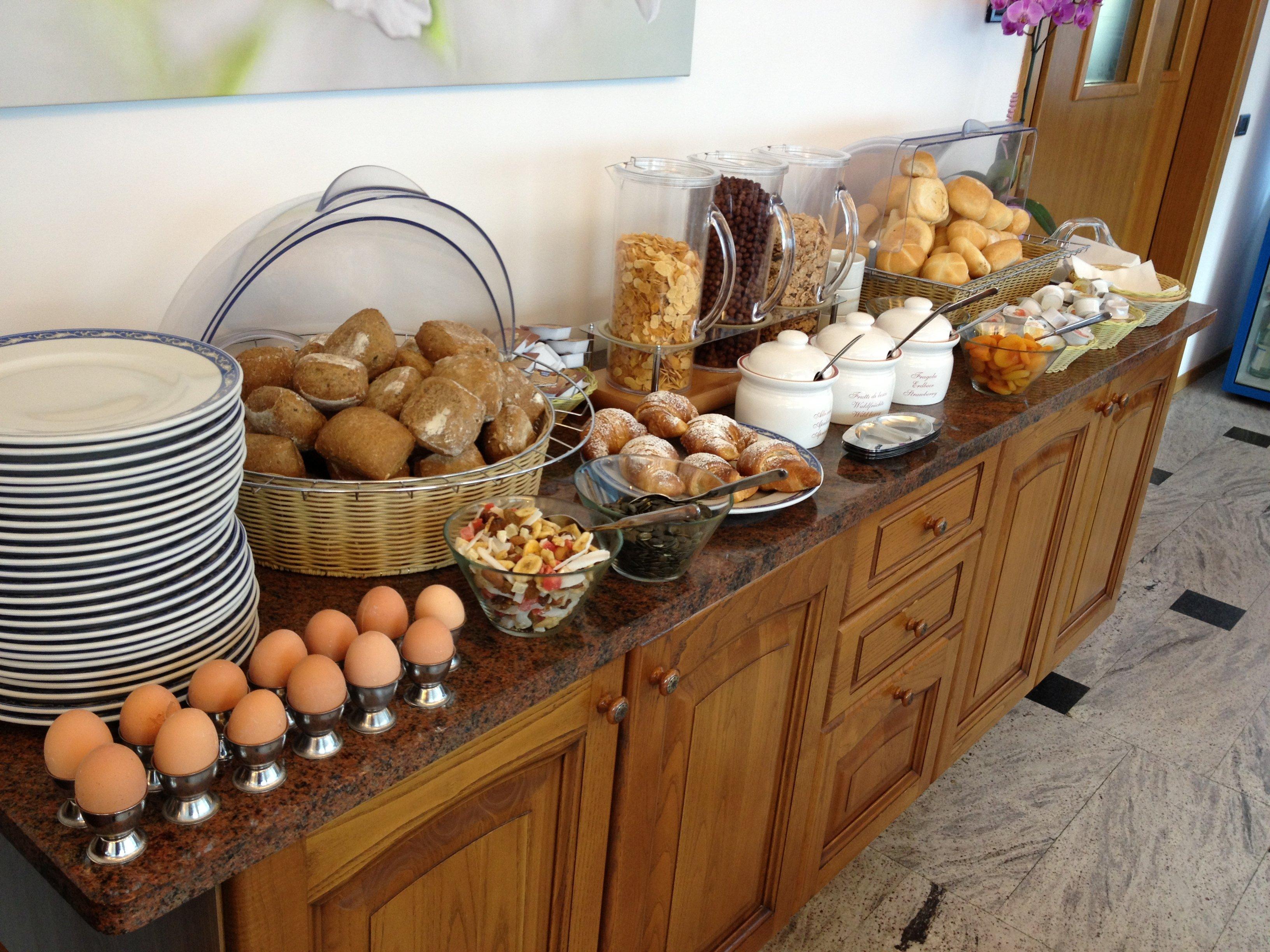 Buffet con piatti, uova, pane fresco, cereali e marmellate