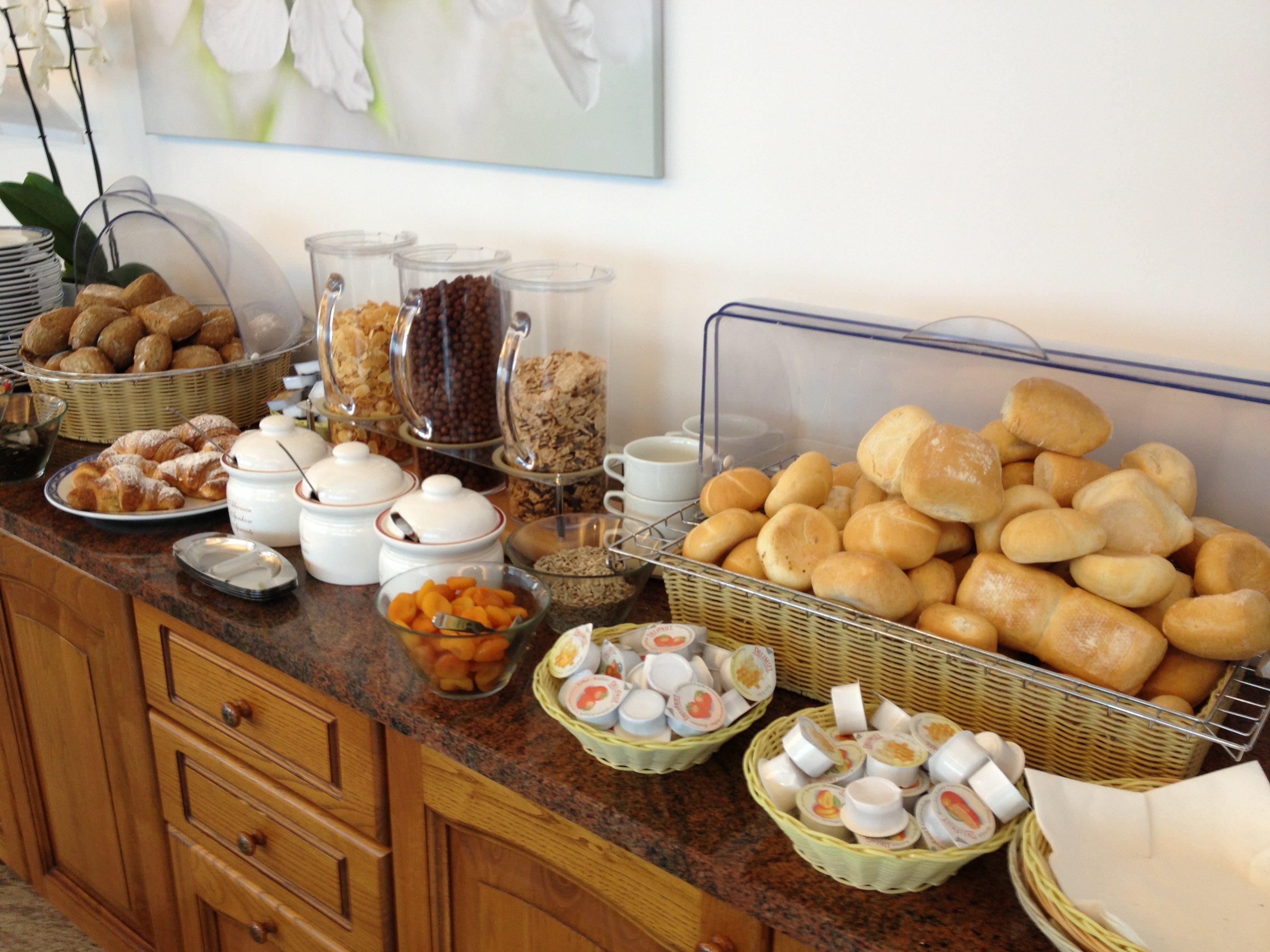 Buffet con pane fresco, marmellate e cereali