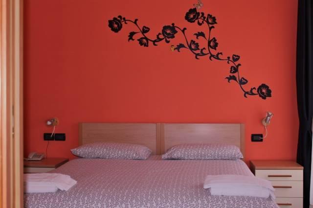 Letto matrimoniale con muro rosso decorato con una composizione floreale