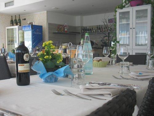 tavolo apparecchiato con bottiglia di acqua e di vino