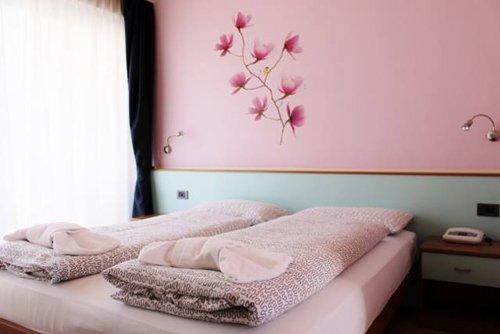 stanza con muri rosa e un fiore dipinto sulla parete