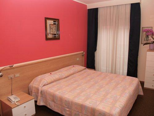 letto matrimoniale con muri rosa e quadro appeso sopra il letto