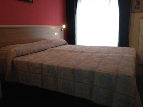 stanza matrimoniale illuminata con tende scure