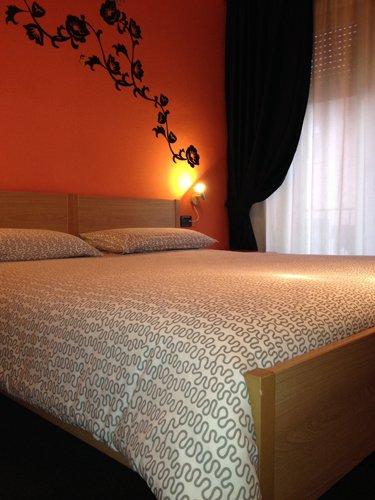 stanza matrimoniale con muro arancione e decorazioni