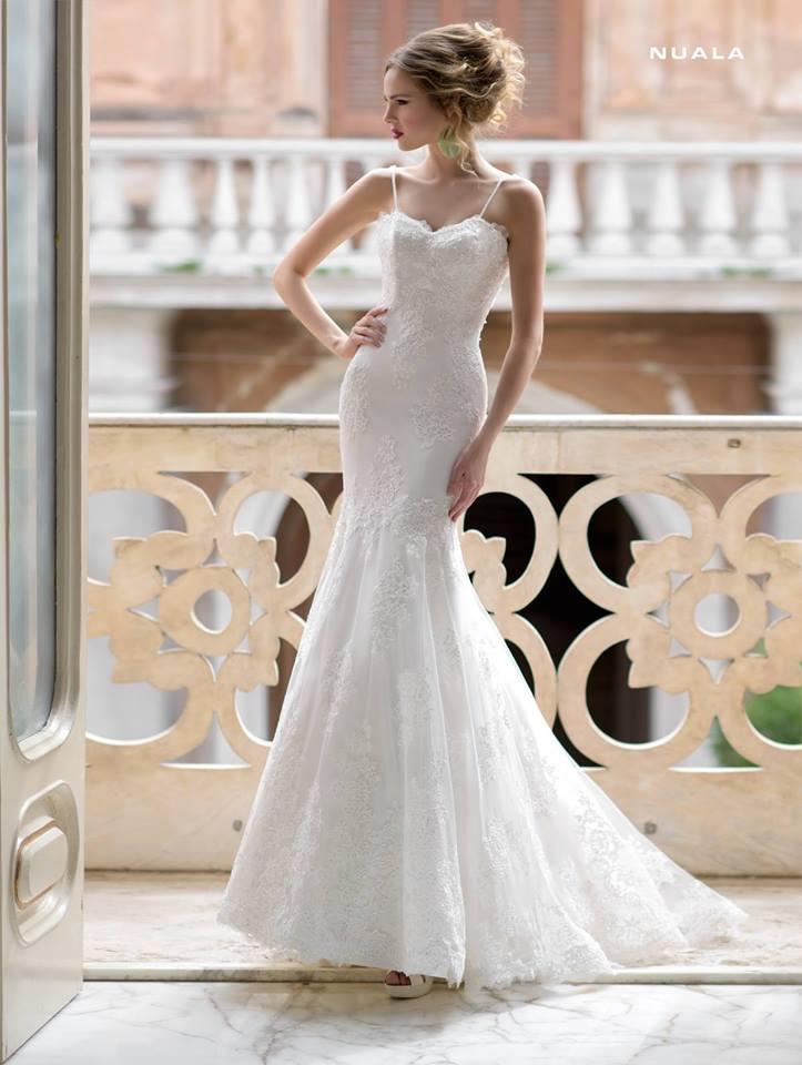 vista frontale di una donna in abito da sposa in un balcone di una casa con capelli bionde